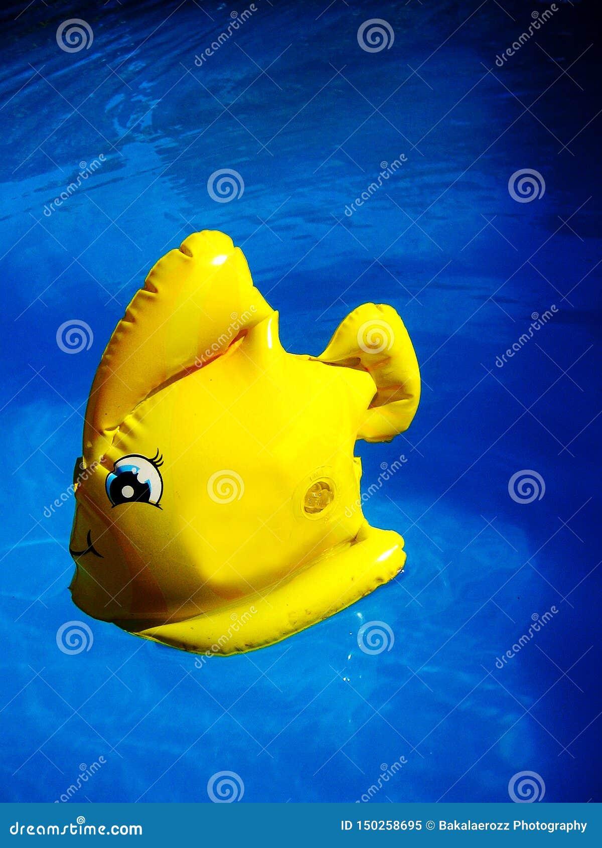 Förbluffa den gula leksakfisken i djupblå konst för tapet för simbassängvattenmakro