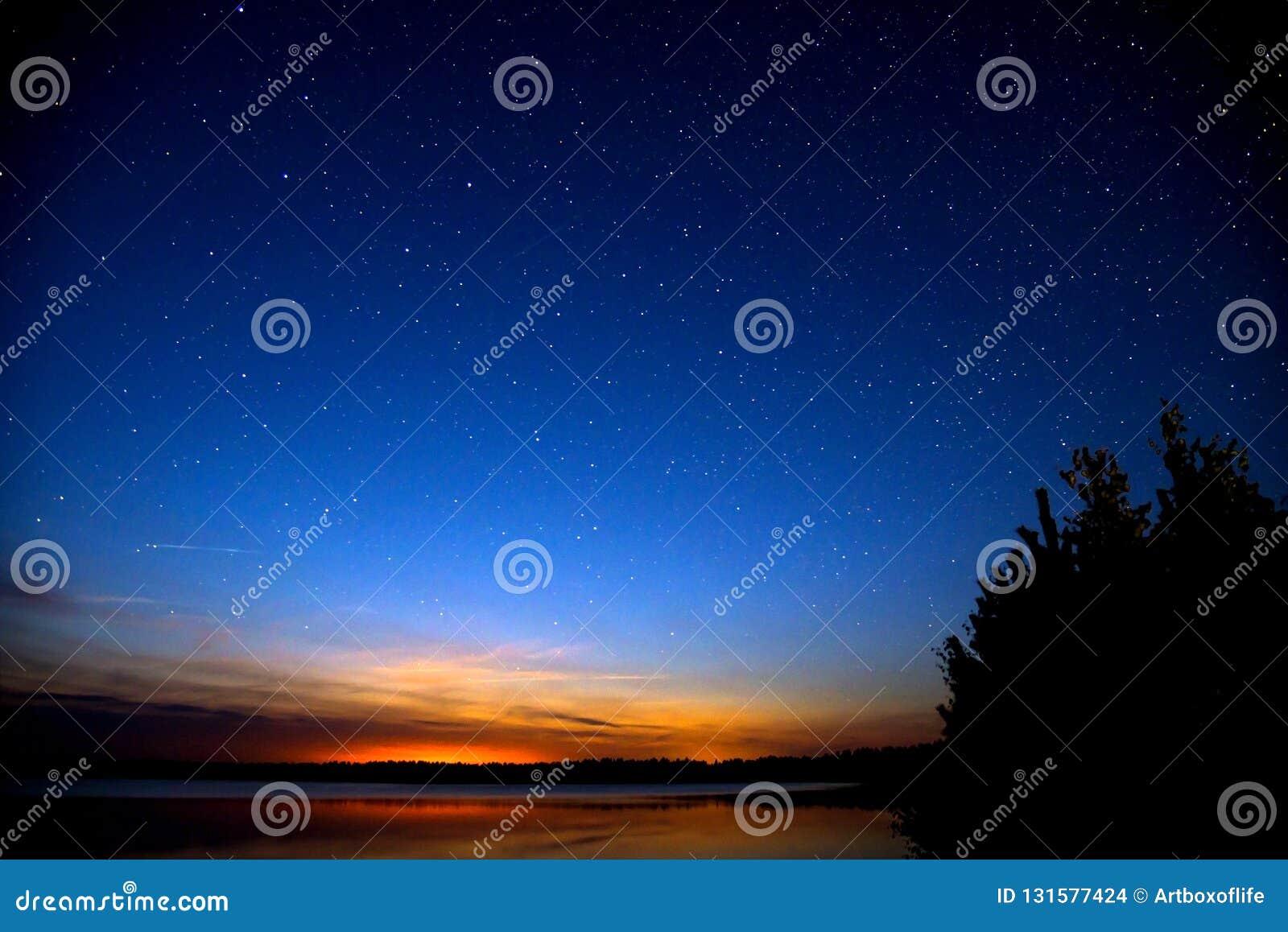 Förbluffa färgrik himmel efter solnedgång vid floden Solnedgång och natthimmel med många stjärnor