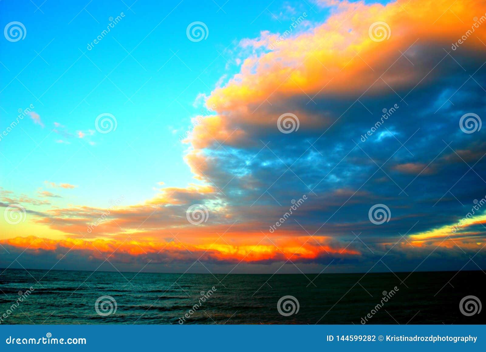 Förbluffa moln över havet under solnedgång