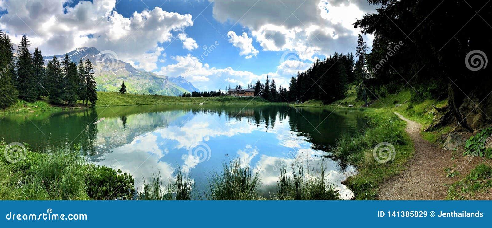 Förbluffa sikt av en liten bergsjö, spegeleffekt