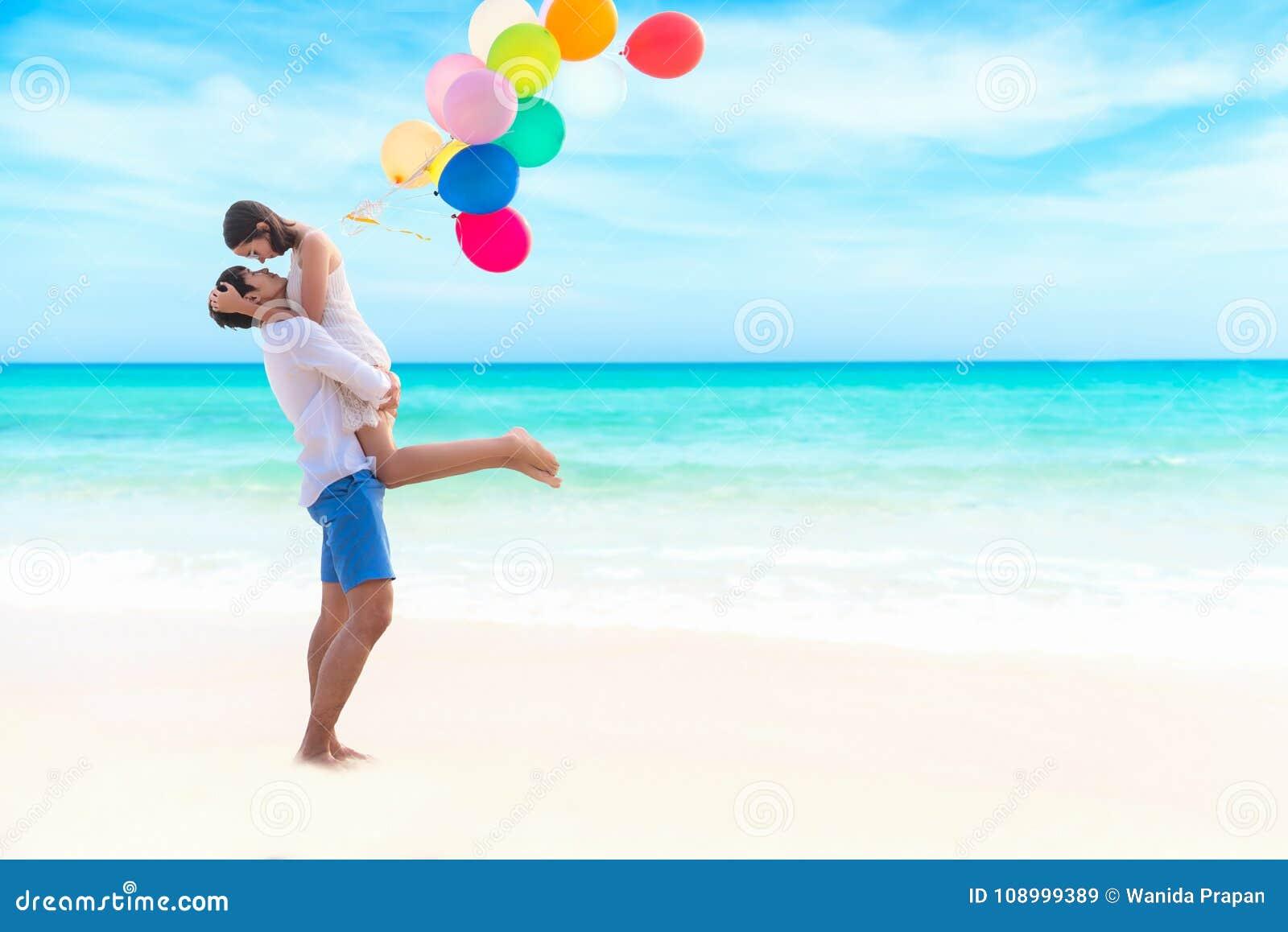 Förbunden förälskelse Att le den asiatiska unga mannen är den hållande flickvännen i hans armar på stranden med den mång- färgbal