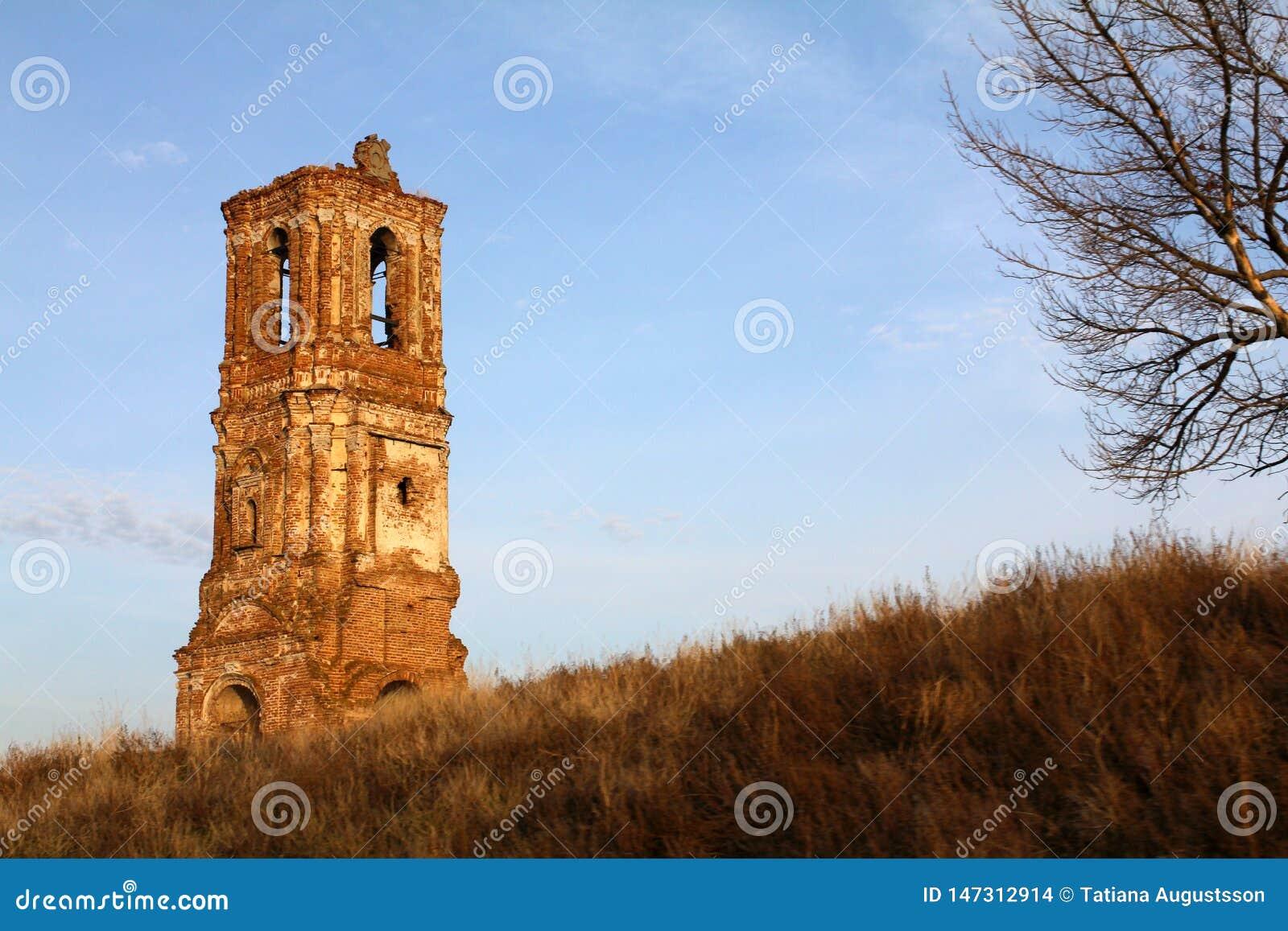 Fördärvar av ortodox gammal kyrka av röd tegelsten och trä mot bakgrunden av landskapet och den blåa himlen i morgonen