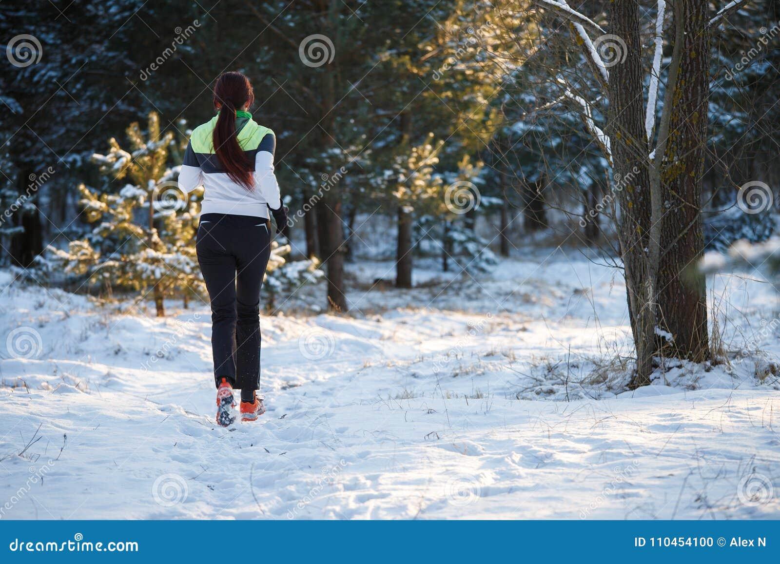 Föreställa från baksida av den unga idrottsman nen som går till och med vinterskog
