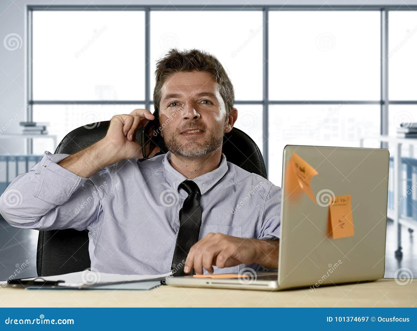 Företags stående av den lyckliga lyckade affärsmannen i skjorta och bandet som ler på datorskrivbordet med mobiltelefonen