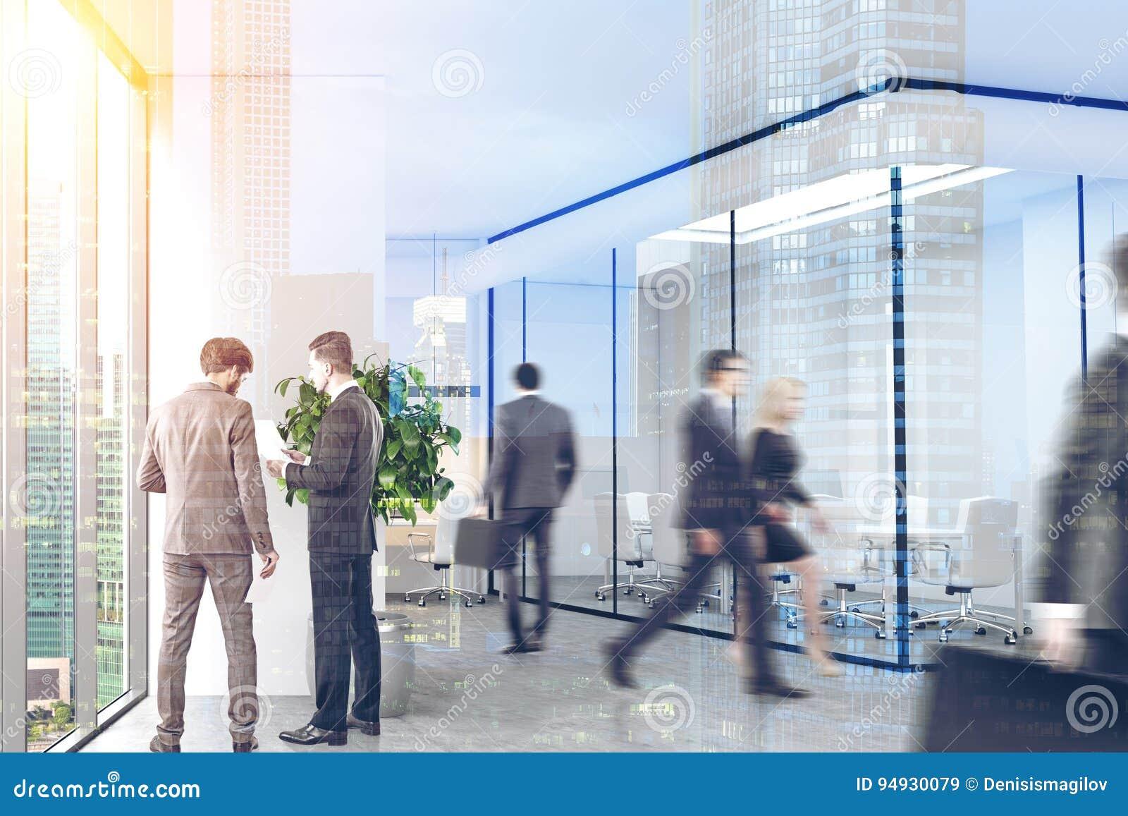 Företagsanställda är gå och tala i ett modernt kontor med vit och glasväggar, betonggolvet och panorama- fönster