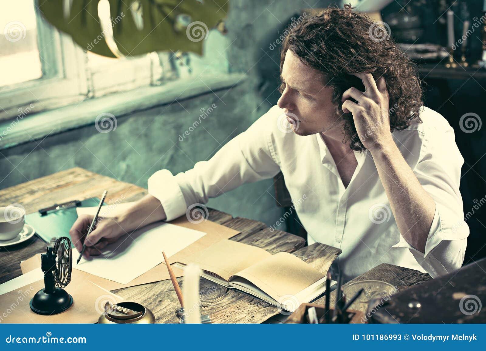 Författare på arbete Stiligt ungt författaresammanträde på tabellen och handstilen något i hans sketchpad