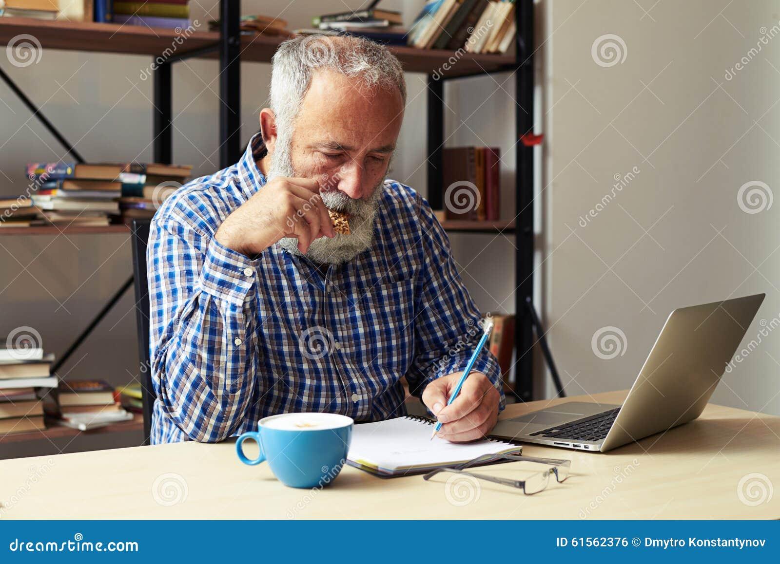 Författare som äter kakor och arbete i hans rum