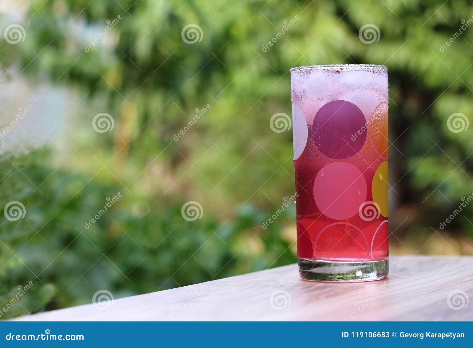 Förkylning rosa fruktsaft med is i en glass kopp för droppe på ett trä i den gröna trädgårds- bakgrunden