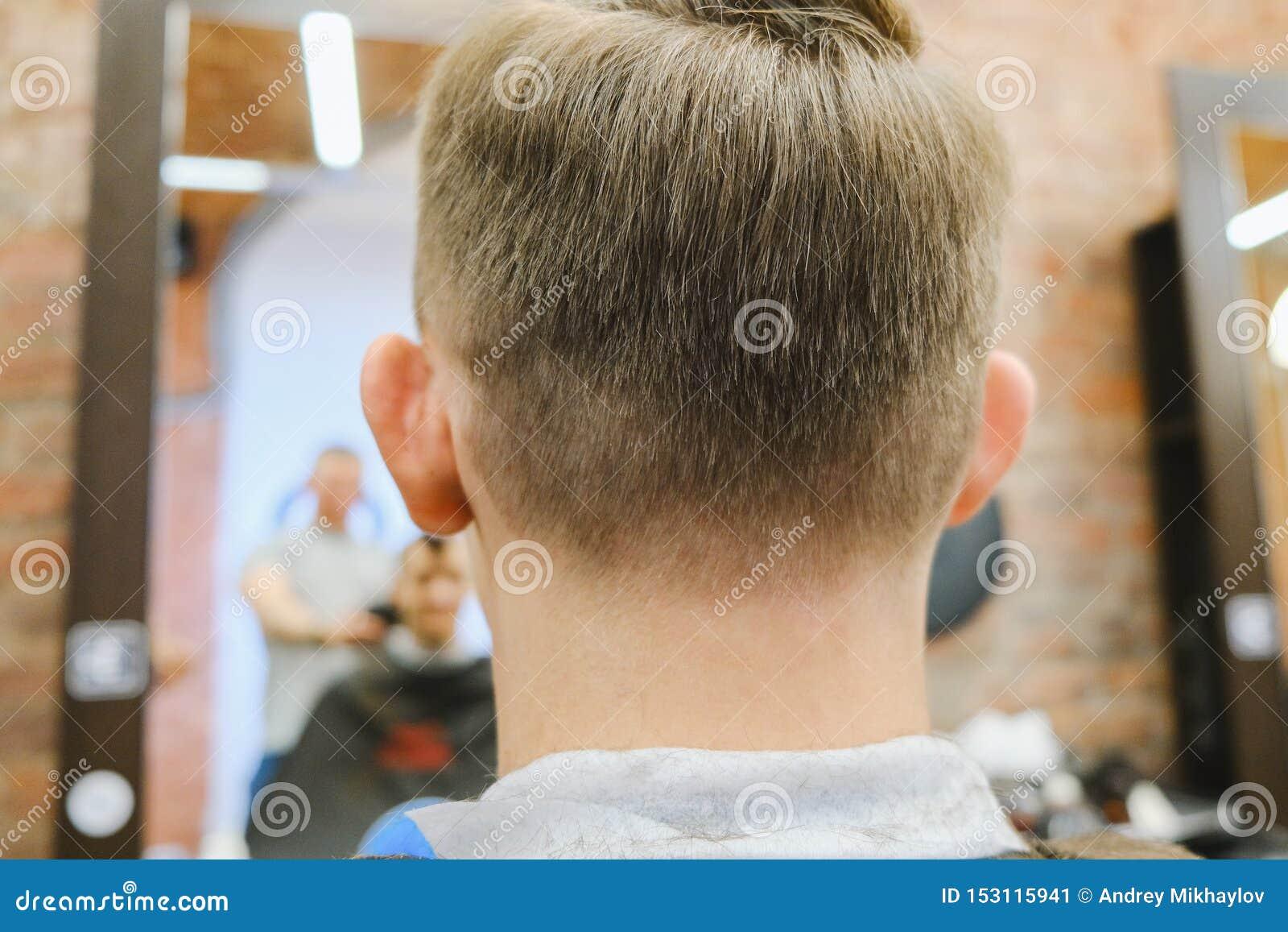 Förlage av frisyrer på arbete Lyckliga grabbar som får frisyr av frisören