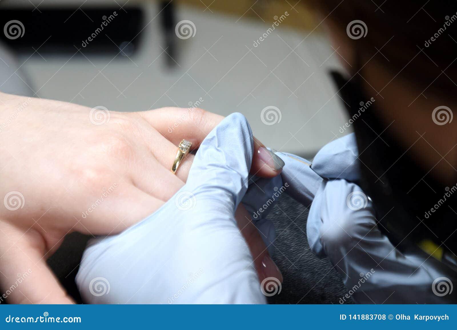 Förlagen gör en manikyr Avslappnande dag på skönhetsalongen Manikyristförlagen gör manikyr på handen för kvinna` s Flickamålarfär
