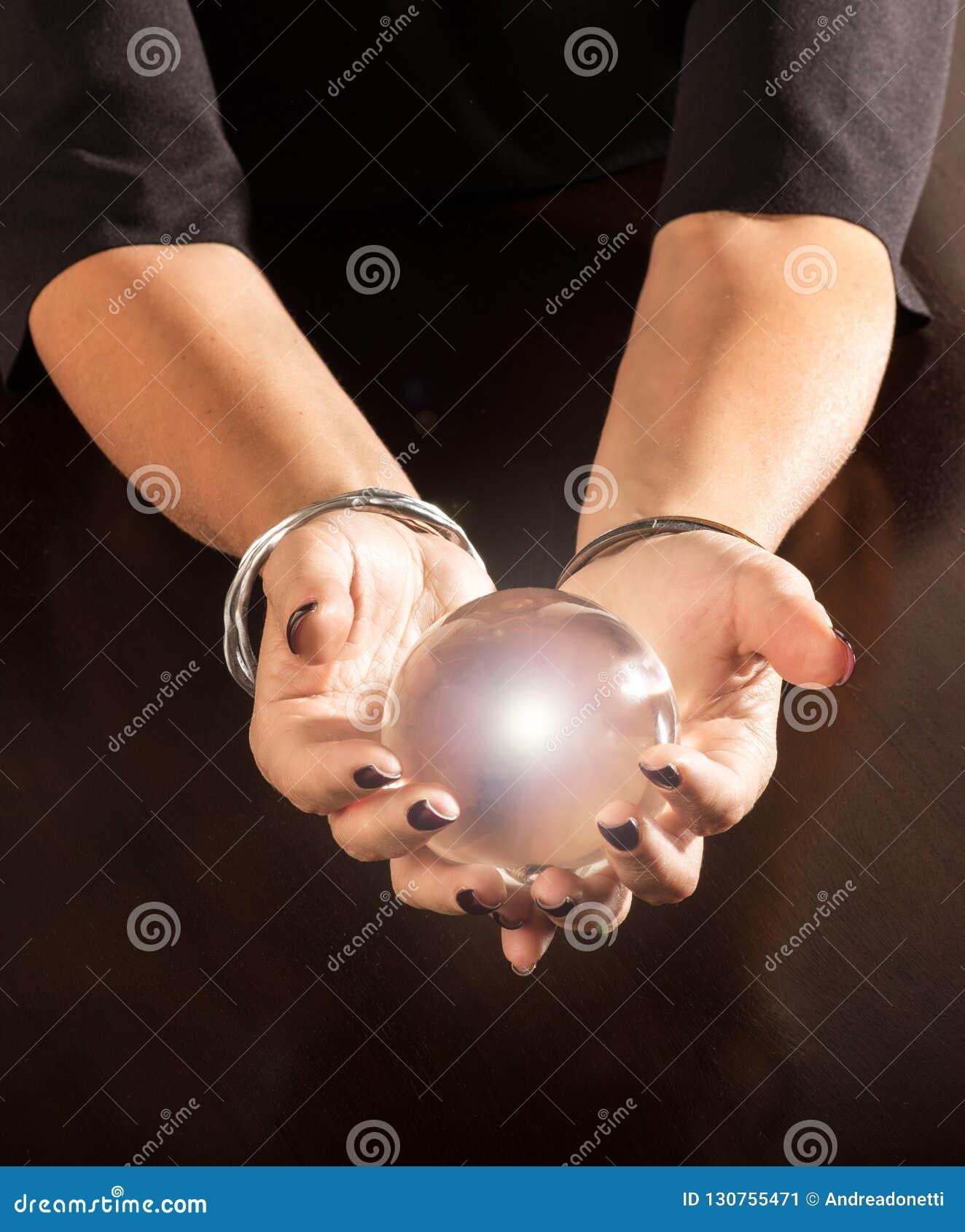 Förmögenhetkassör som rymmer en kristallkula i hennes händer