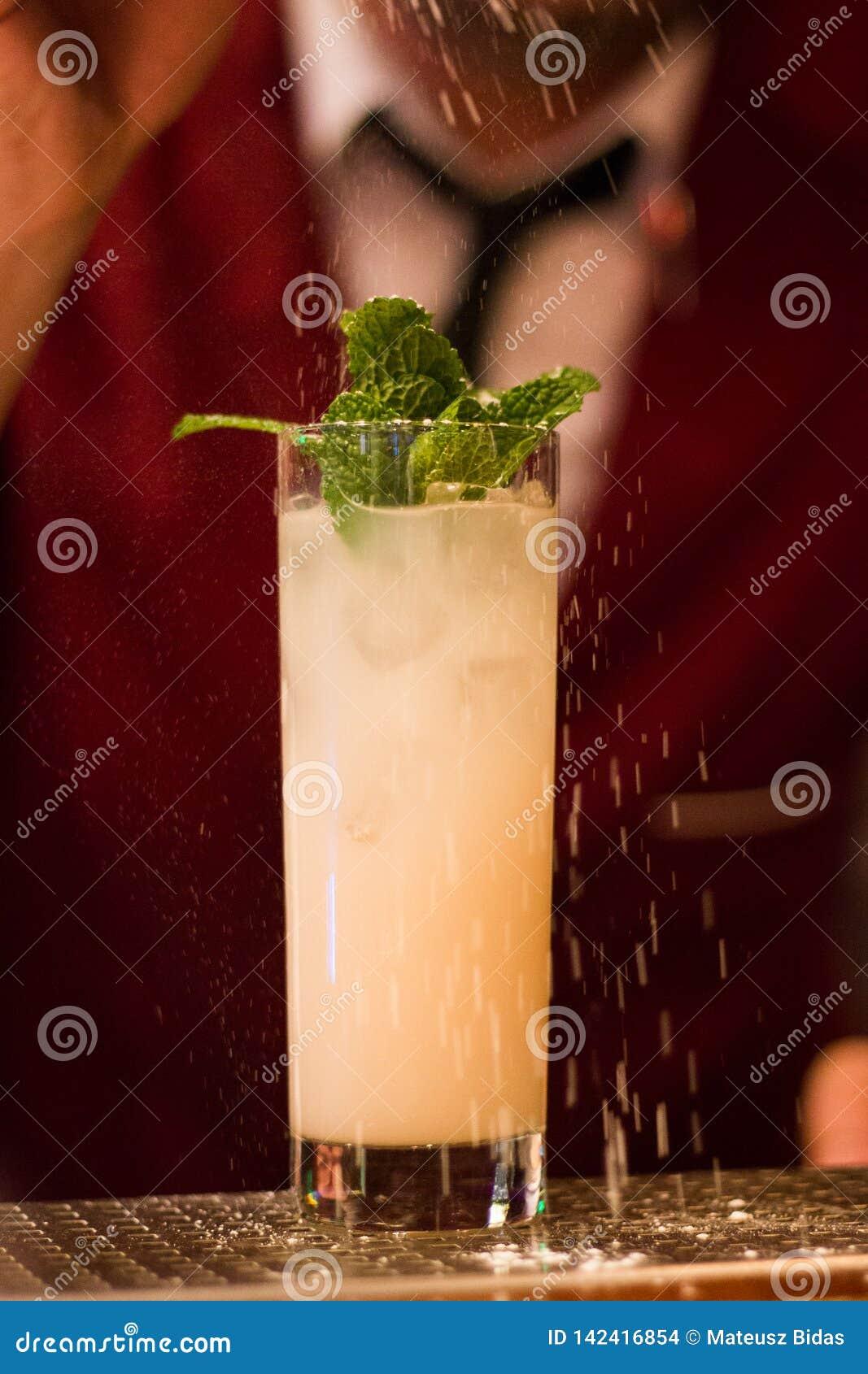 Förnyande coctail som täckas i snö med bartendern i band