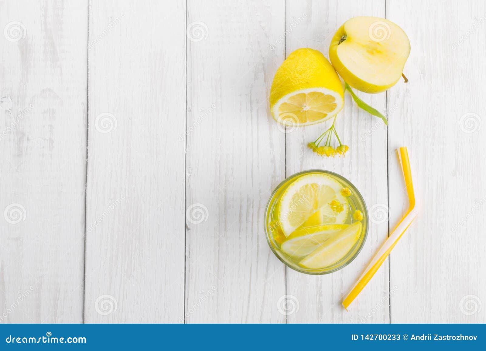 Förnyande drink för detoxification, citronvatten i ett exponeringsglas, nytt äpple och gula lindblommor på en vit tabell