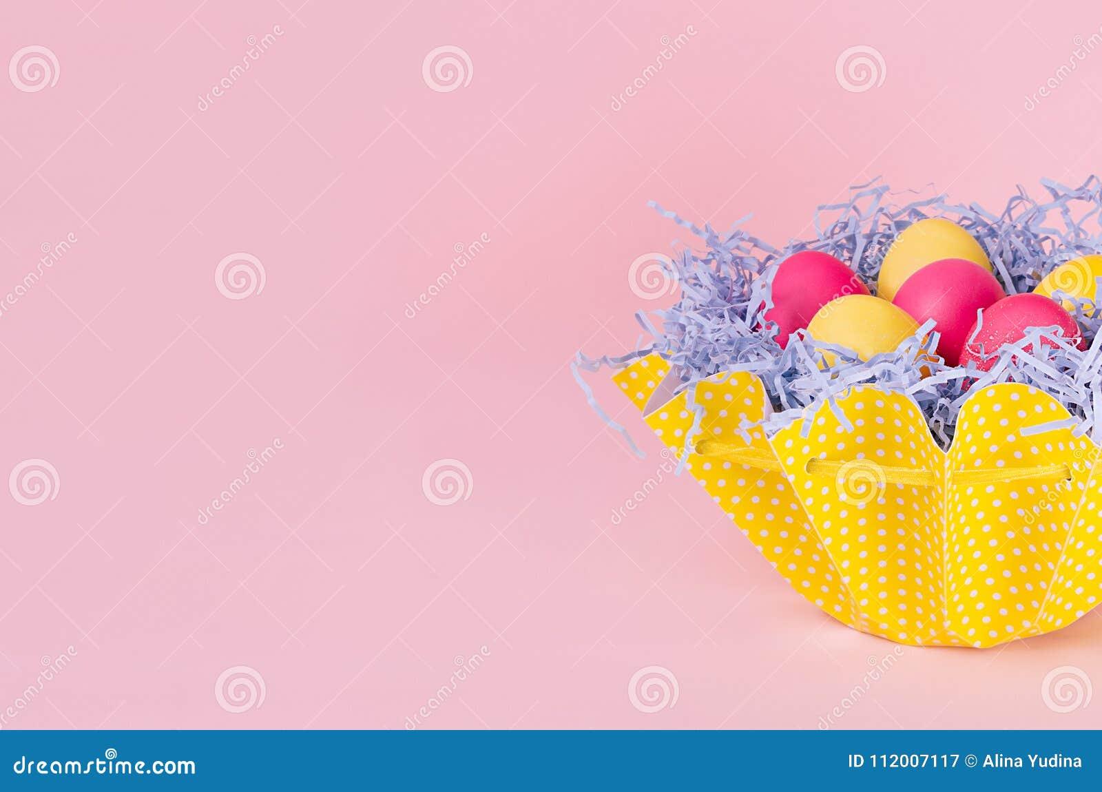 Försiktig elegant mjuk rosa easter garnering - målade ägg i gul korg på rosa bakgrund