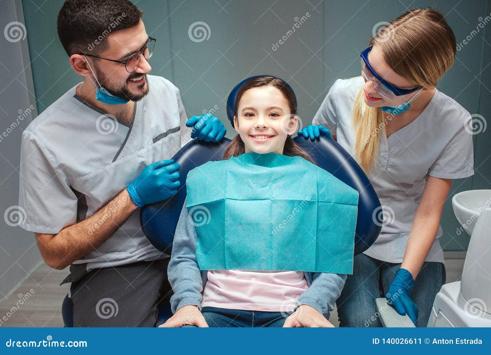 Försiktig positiv man och kvinnlig tandläkareblick på det ungepatienten och leendet Flickan sitter i tand- stol Hon ser rak och