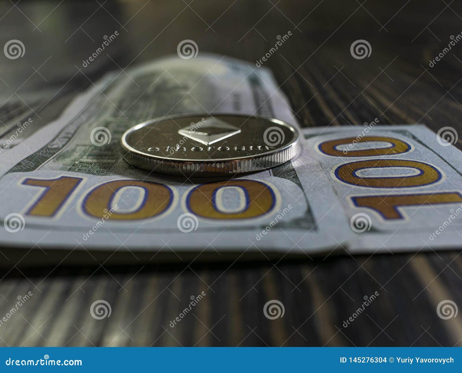 F?rsilvra Ethereum p? US dollar Digital valutan?rbild p? en tr?bakgrund Verkliga mynt av bitcoin p? sedlar av hundra