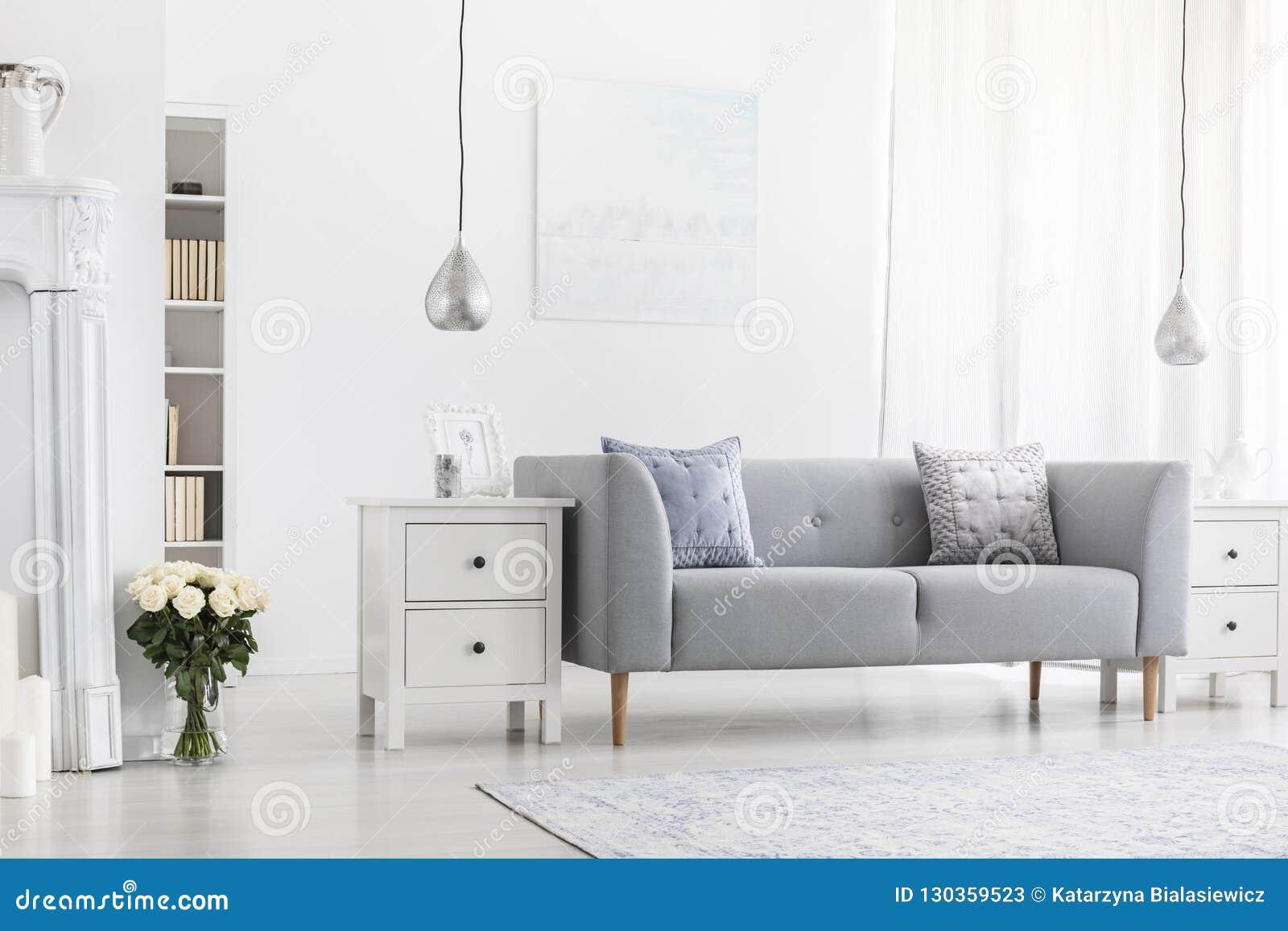 Försilvra lampor ovanför vita kabinetter i lägenhetinre med blommor och den gråa soffan Verkligt foto