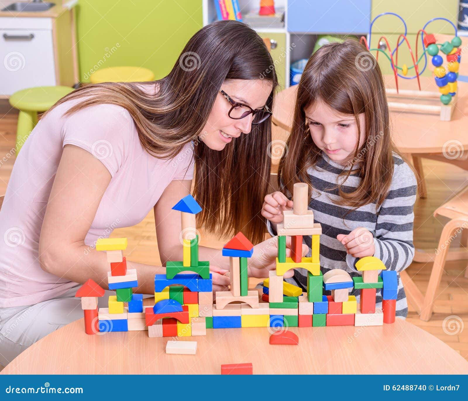 Förskole- lärare Instructs Cute Girl hur man bygger Toy Castle