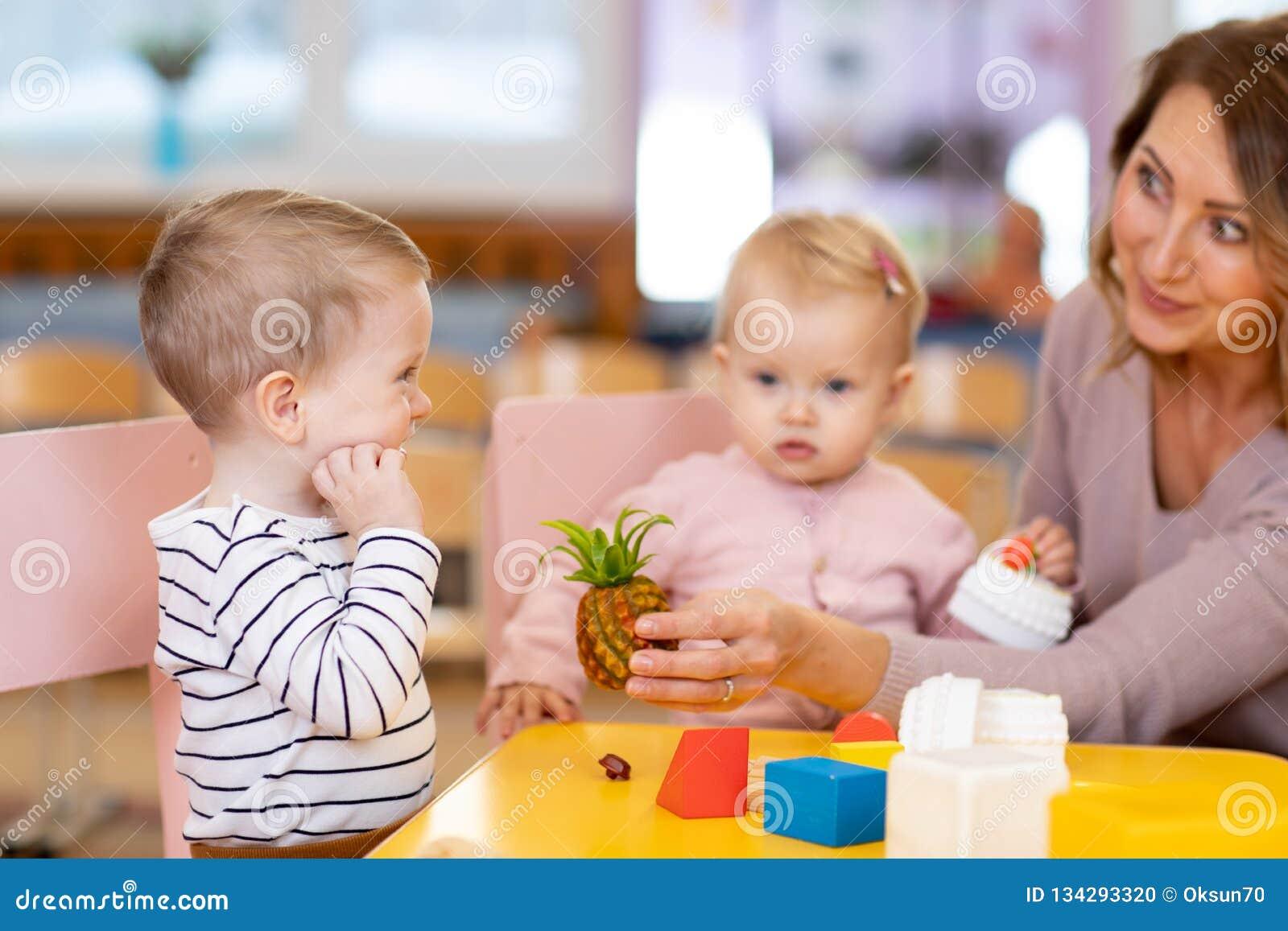 Förskole- lärare med barn som spelar med färgrik leksaker på dagiset