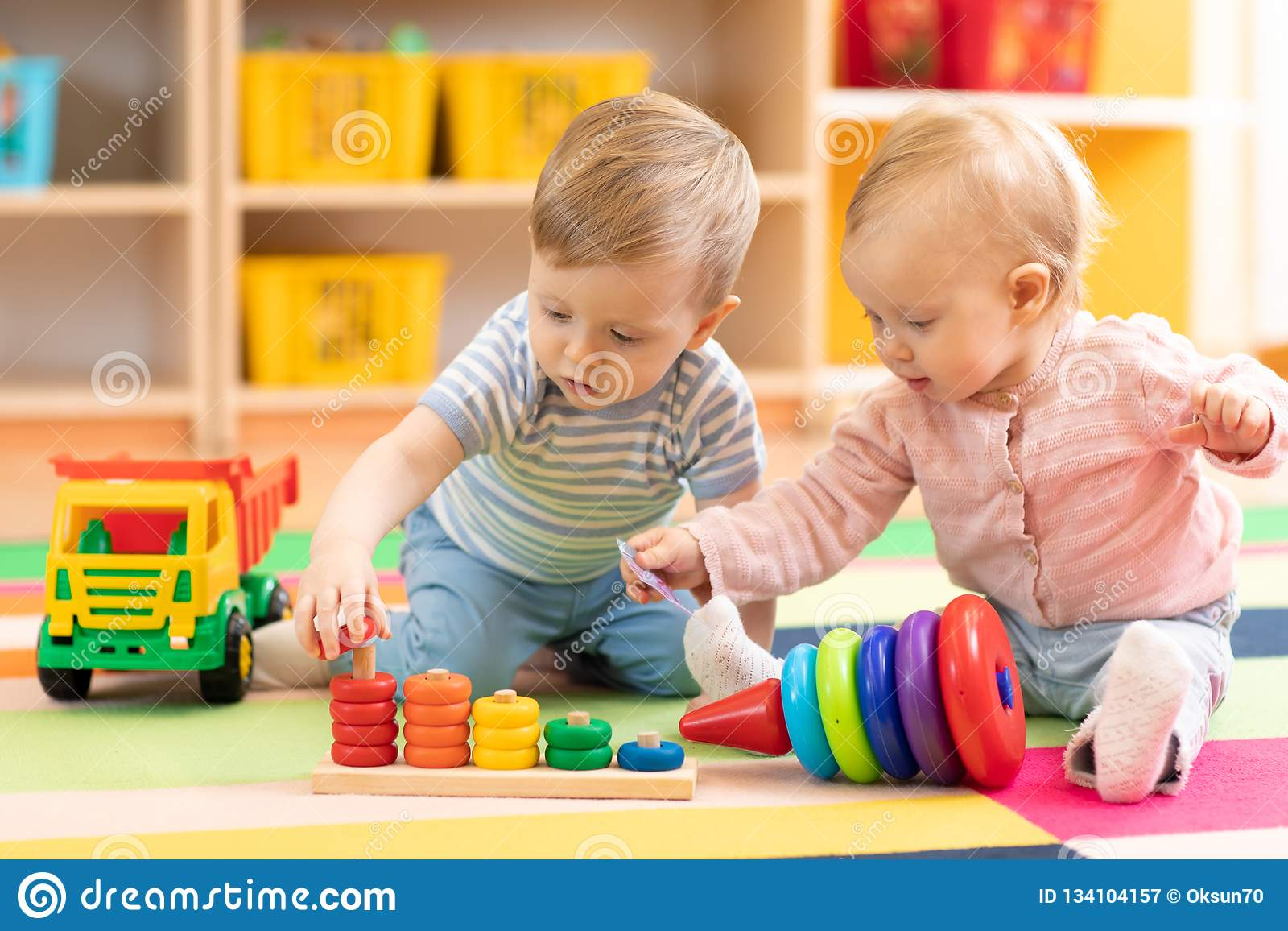 Förskole- pojke och flicka som spelar på golv med bildande leksaker Hemmastadda barn eller daycare