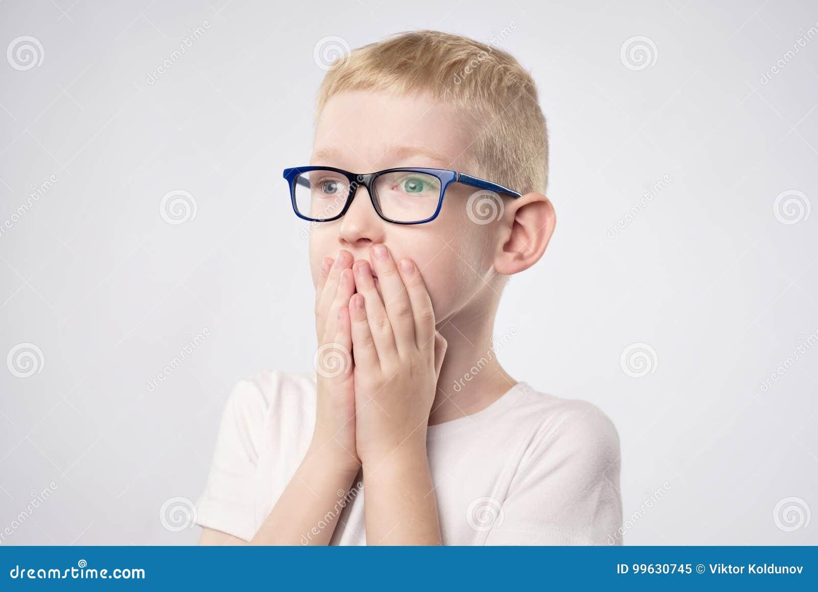 Förskräckt pojke för liten unge med innehavhänder för blont hår på framsida, därför att han är rädd