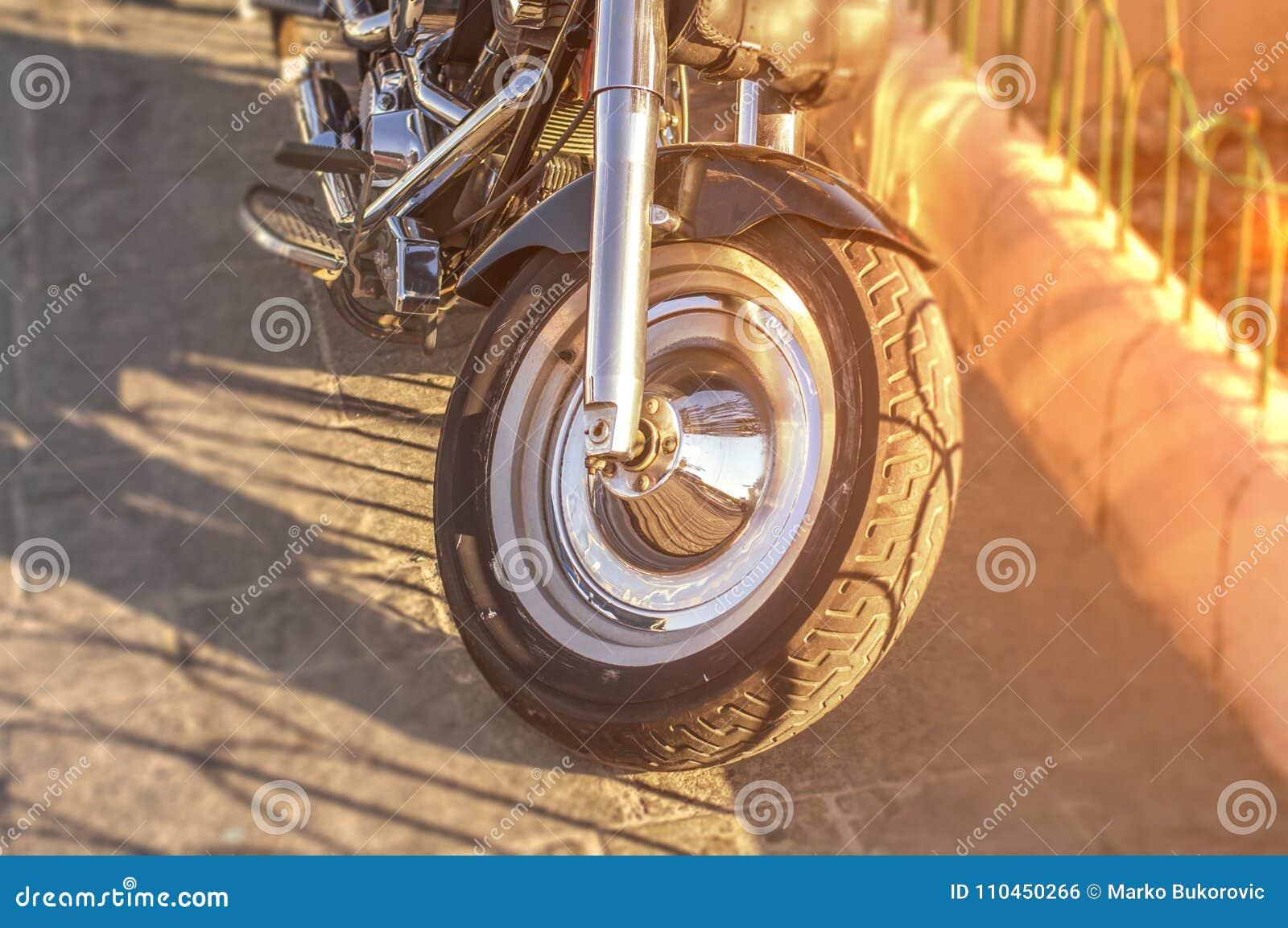 Första hjul för motorisk cykel som parkeras på stadsgatan med den brinnande solen
