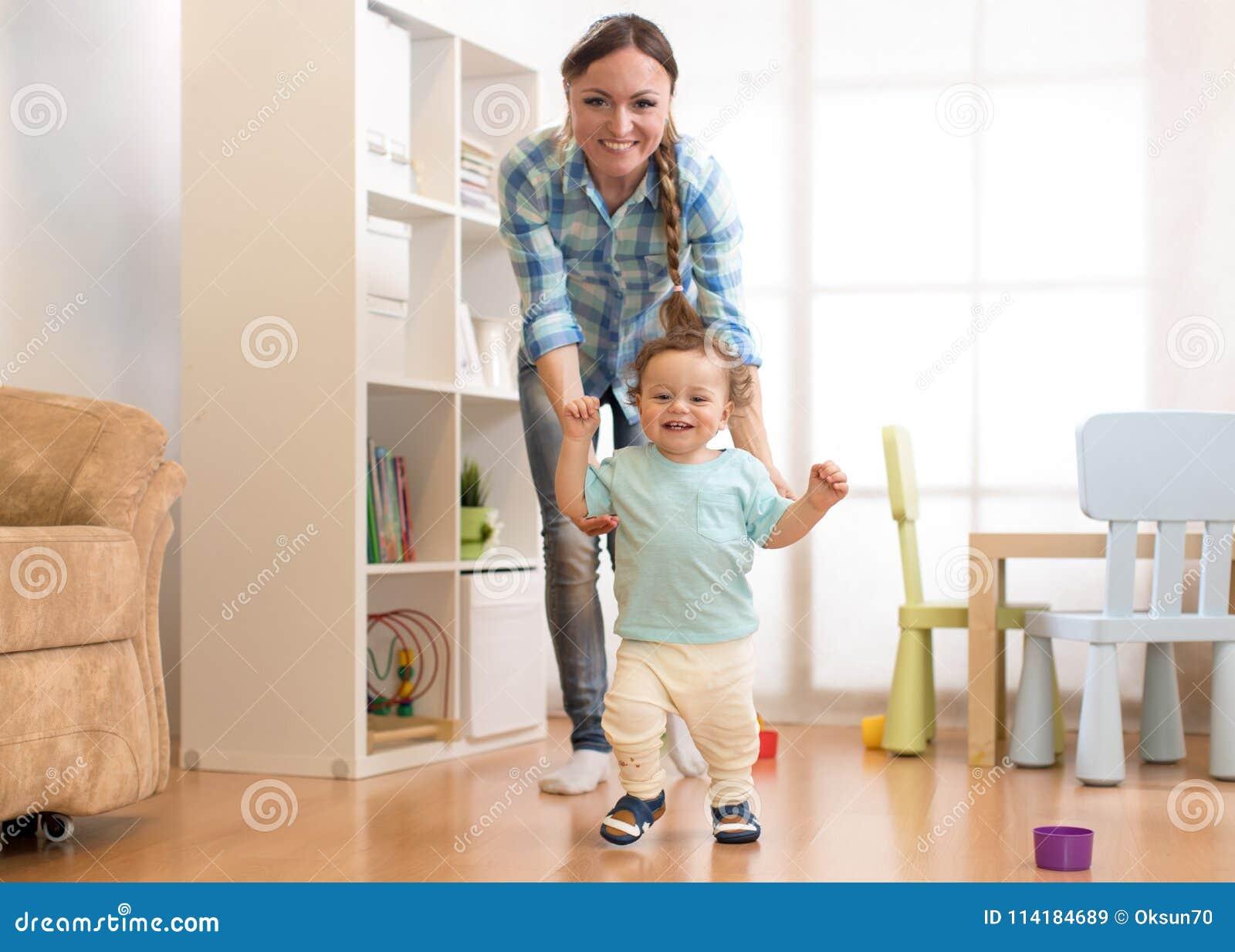 Första steg av behandla som ett barn litet barnpojken som lär att gå i vit solig vardagsrum Skodon för barn