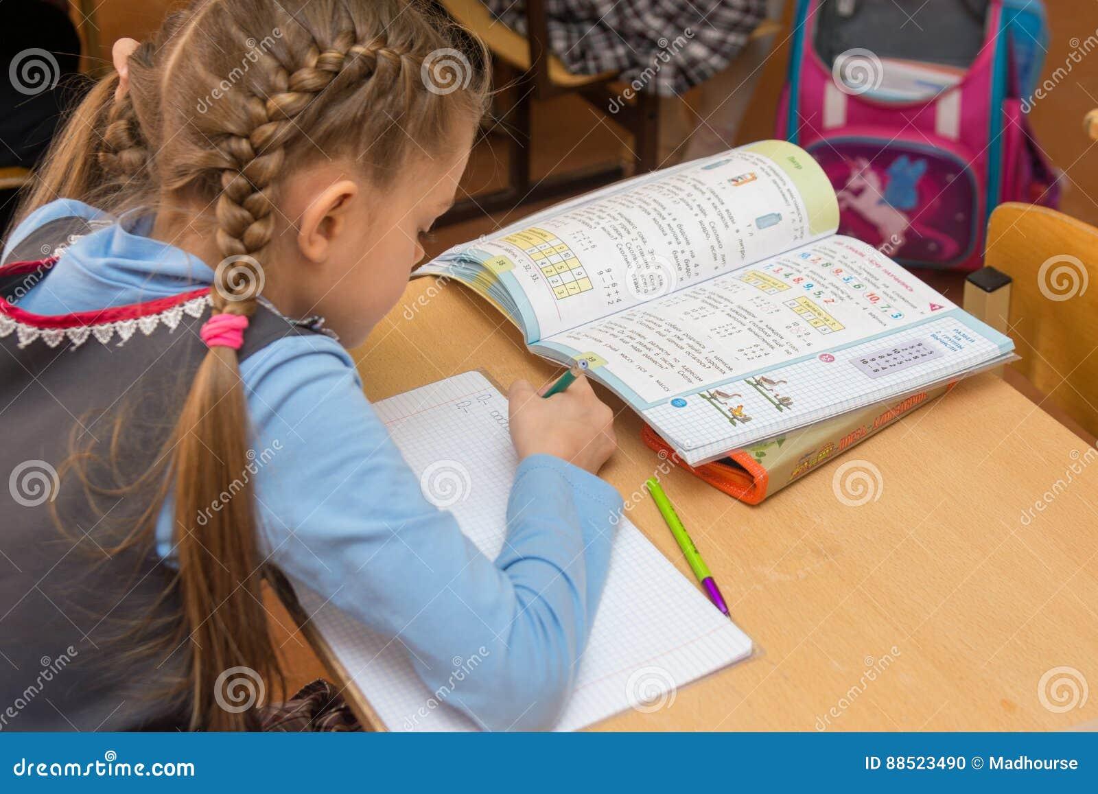 Första-väghyveln på en kurs av matematik skriver i en anteckningsbok, sidosikt från baksidan