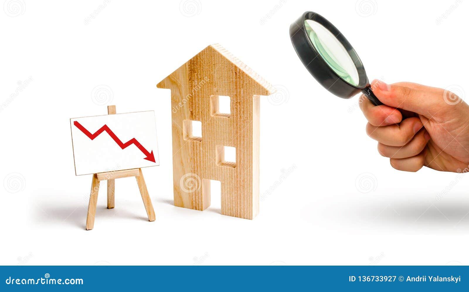 Förstoringsglaset ser trähuset och den röda pilen ner begrepp av fallande priser och begäran för fastigheten, nedgången