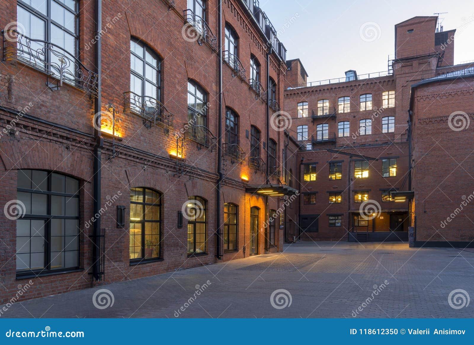 Förtöjd sikt för nattportship Moderna Vind-stil kontor som lokaliseras i den gamla fabriksbyggnaden tegelsten houses red Tappning