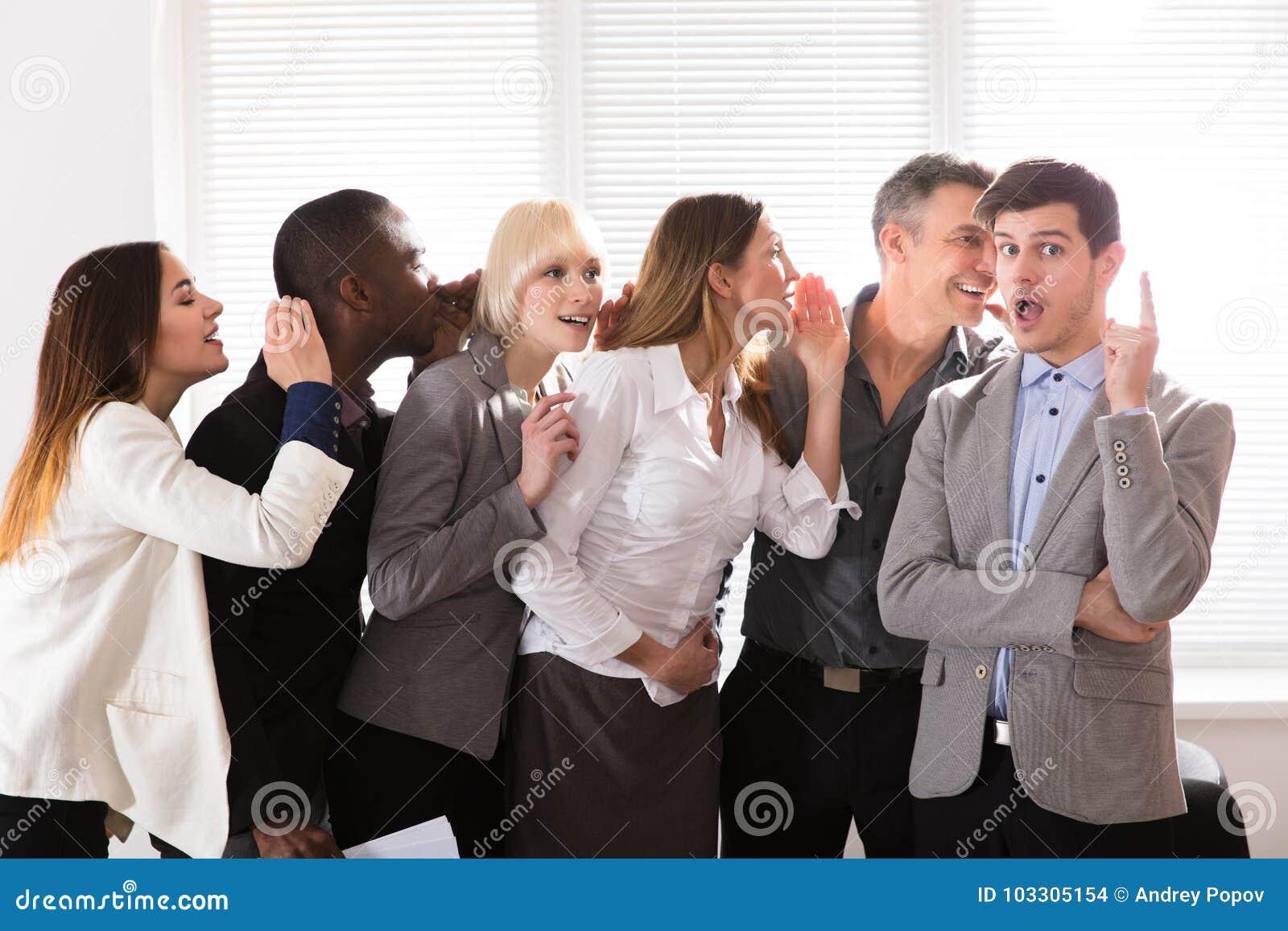 Förtegna affärskollegor som viskar i kontoret