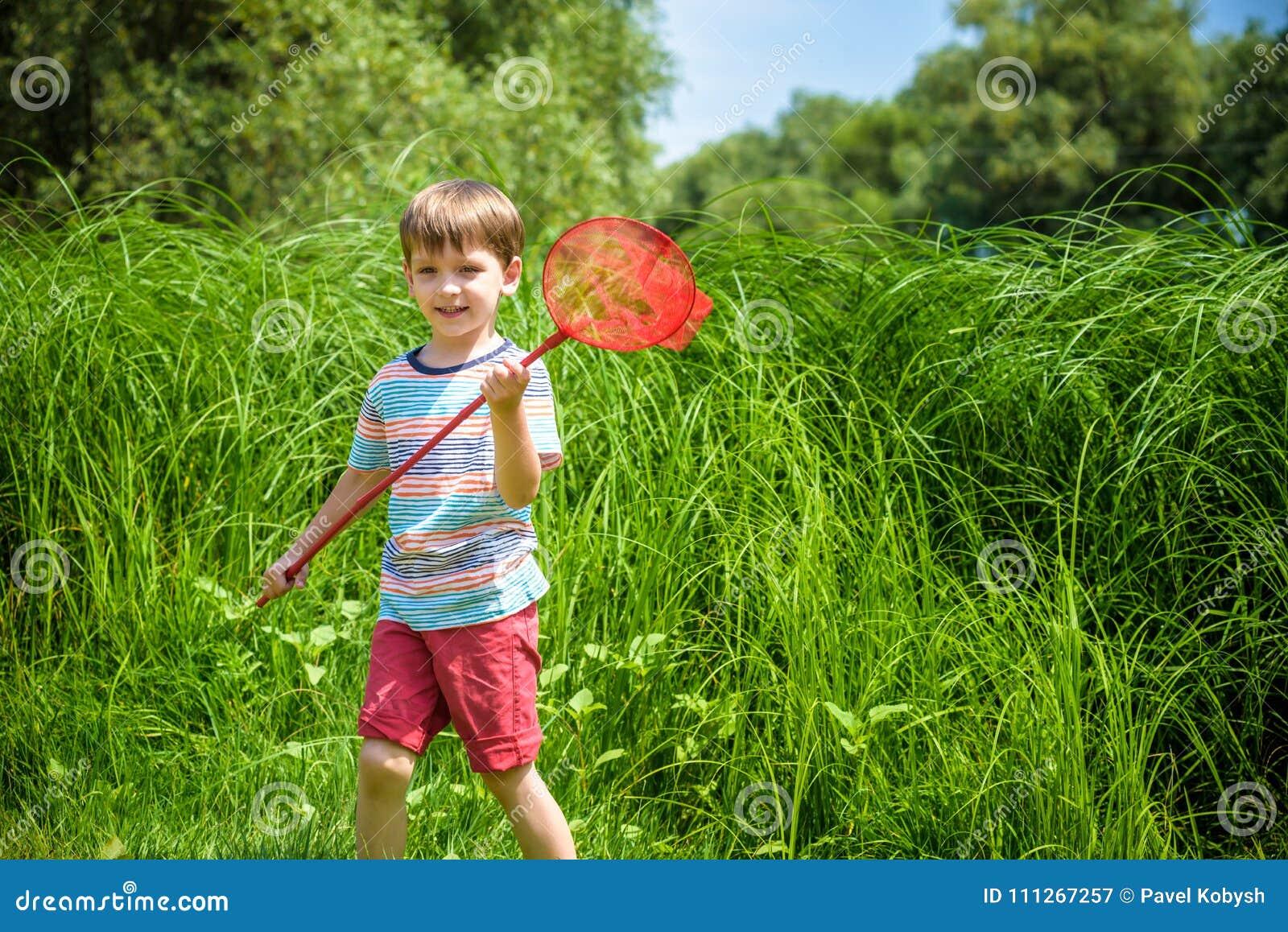 Förtjusande Caucasian unge som spelar med skopa-netto på ängen på varm och solig sommar eller vårdag