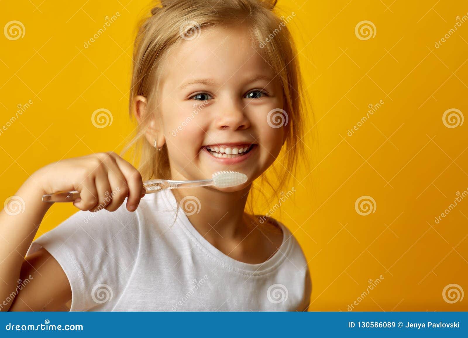 Förtjusande flicka som borstar tänder med ungetandborsten