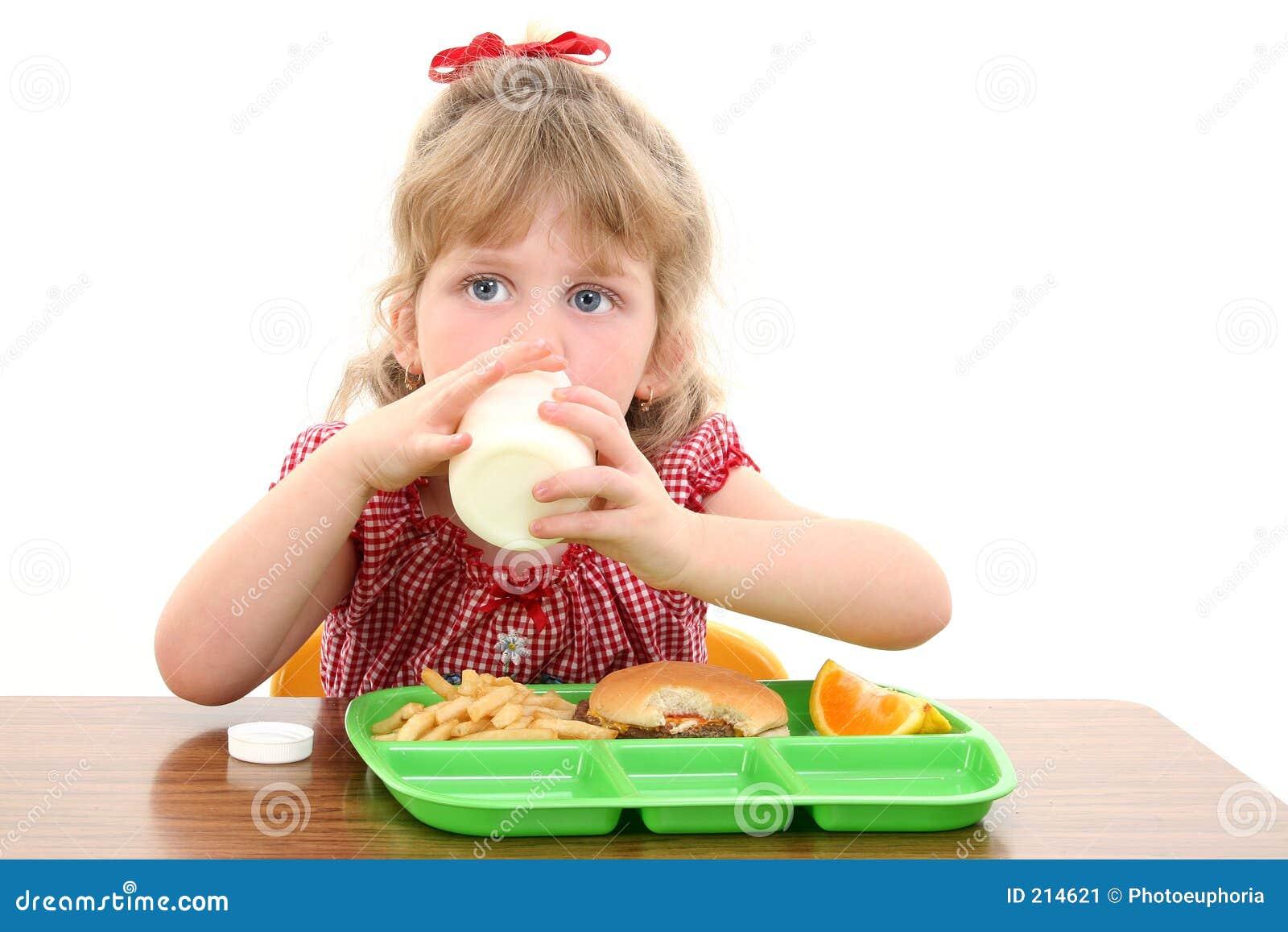 Förtjusande flicka som har little att äta lunch skolan