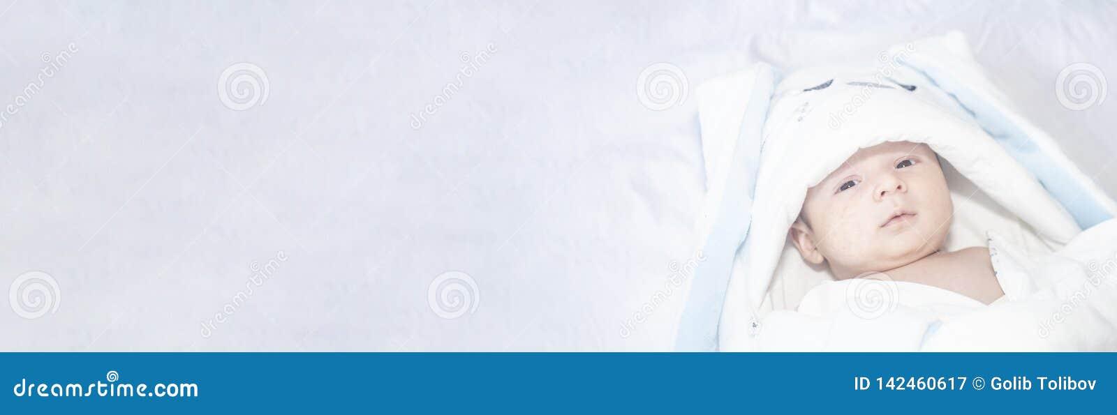 Förtjusande gulligt nyfött behandla som ett barn pojken på vit bakgrund Det älskvärda barnet bar en kanindräkt med långa öron eas