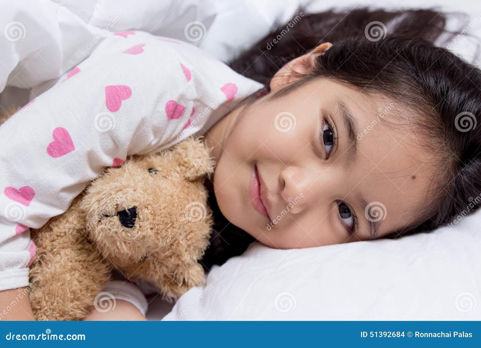 Förtjusande liten asiatisk flickasömn med björndockan