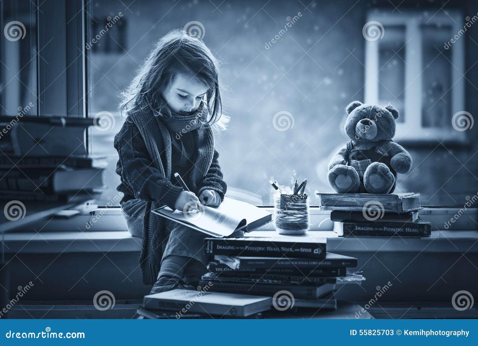 Förtjusande liten flicka och att skriva brevet till jultomten som sitter på en vind