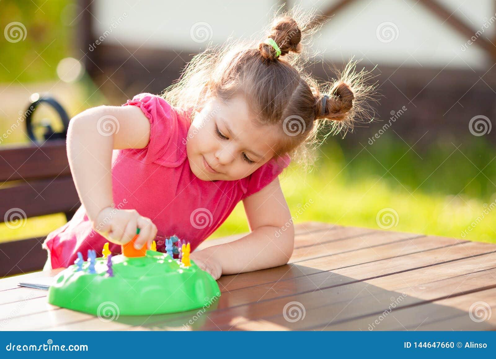 F?rtjusande liten flicka som spelar br?deleken utomhus