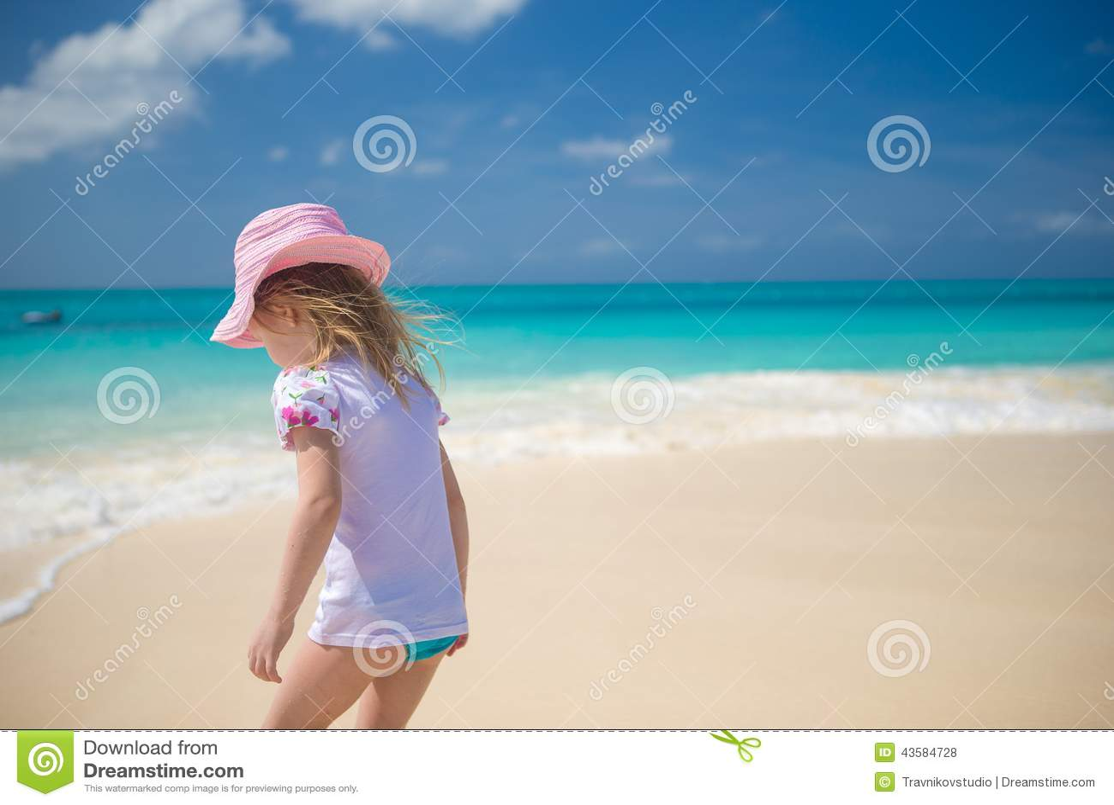 Förtjusande liten flicka som spelar i grunt vatten på