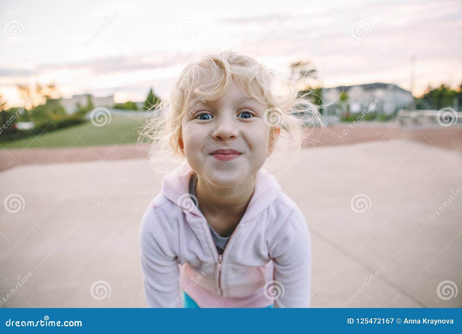 Förtjusande litet blont Caucasian flickabarn som gör den roliga enfaldiga framsidan