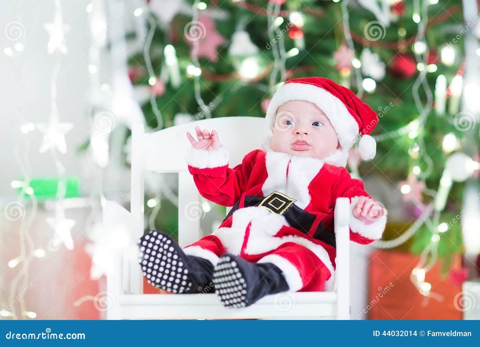 Förtjusande nyfött behandla som ett barn pojken i den Sante dräkten bredvid en härlig julgran