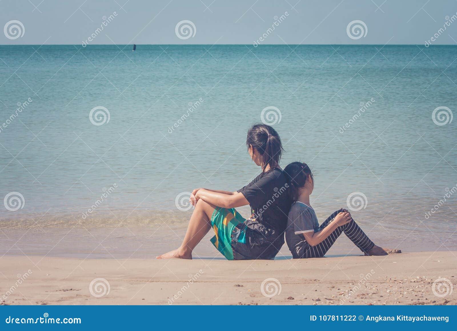 Förtjusande och familjbegrepp: Kvinna och barn som tillbaka sitter för att dra tillbaka på sandstranden