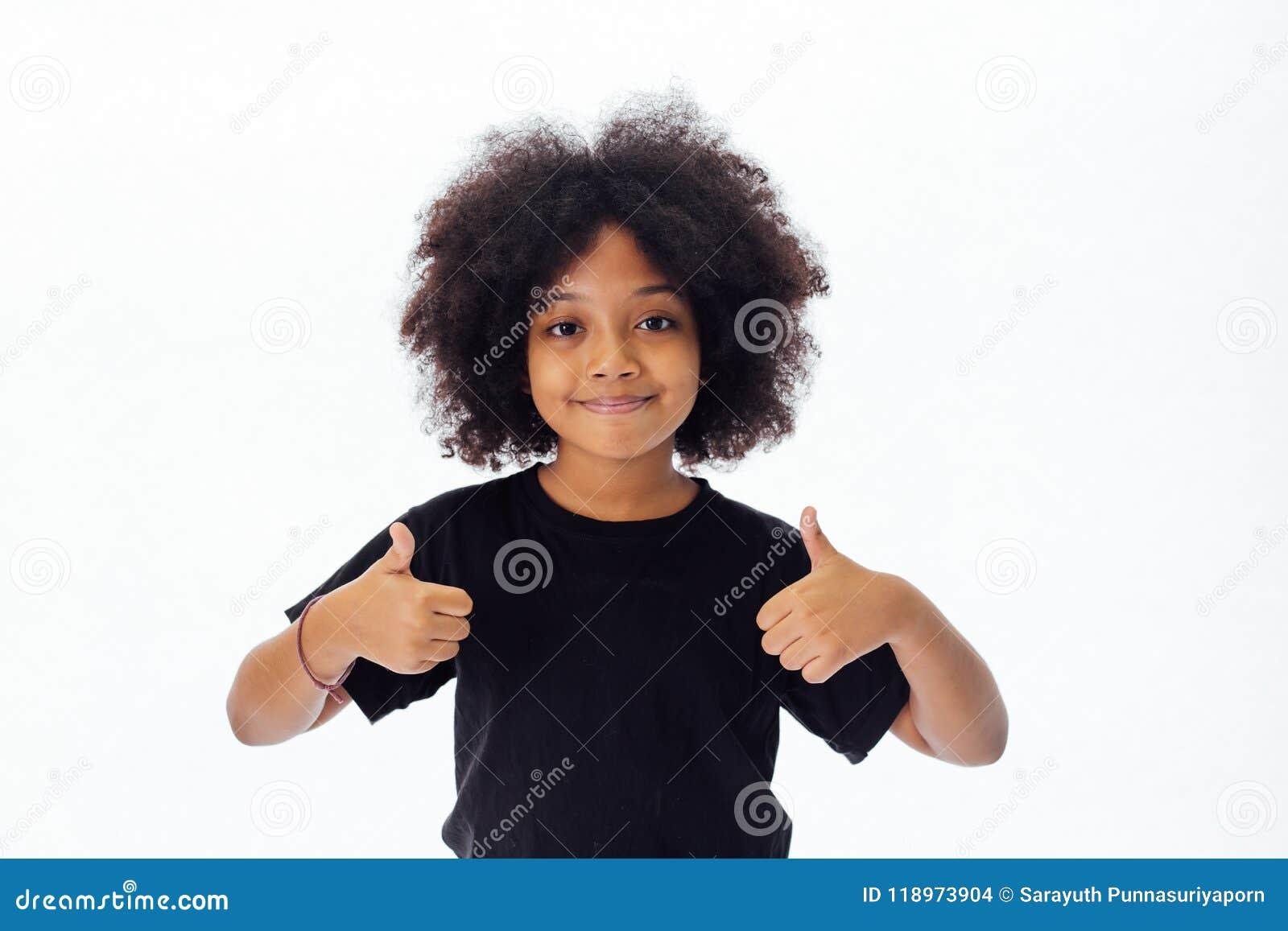 Förtjusande och gladlynt afrikansk amerikanunge med den afro frisyren som ger upp tummar