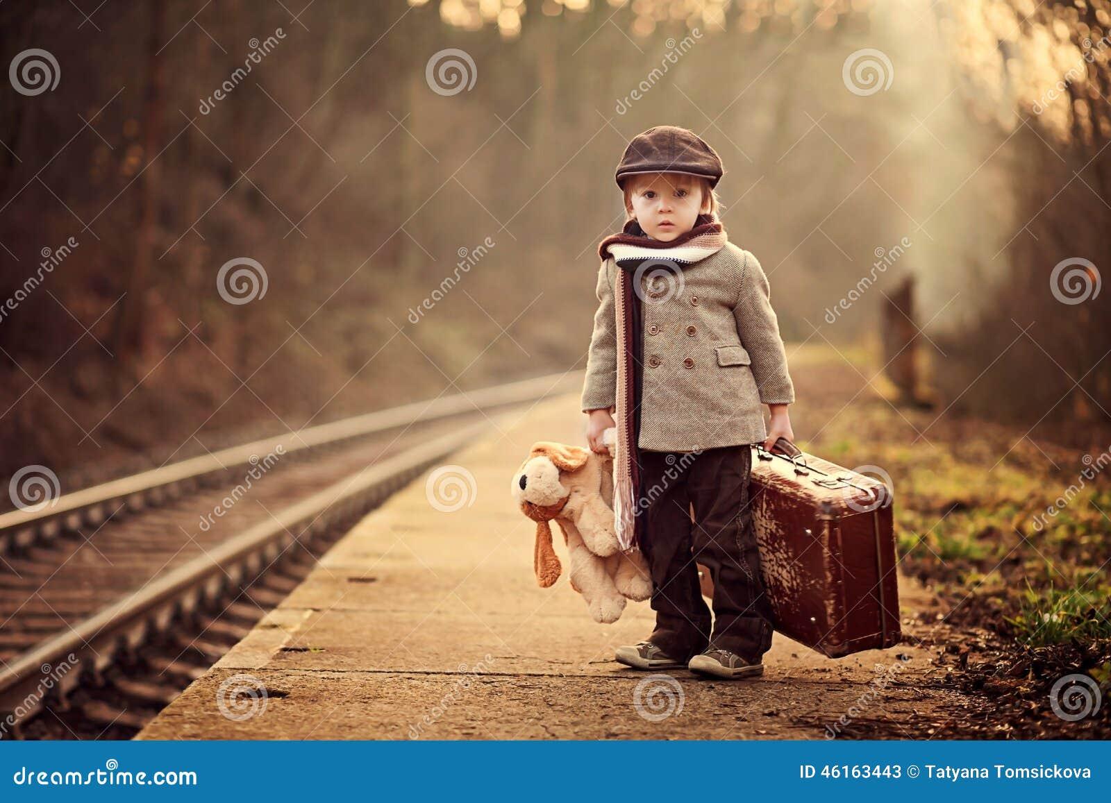 Förtjusande pojke på en järnvägsstation som väntar på drevet