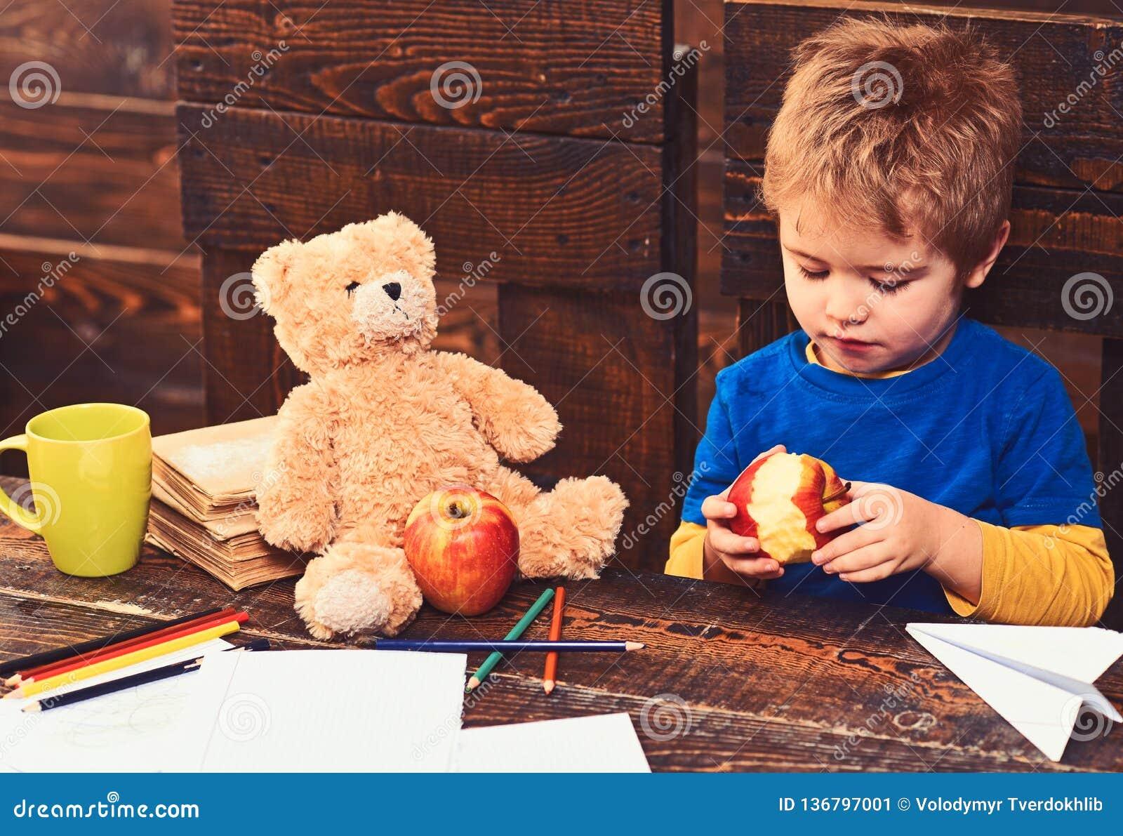 Förtjusande pojke som äter det läckra äpplet Unge som delar mellanmålet med den favorit- leksaken Elev som spelar under avbrott