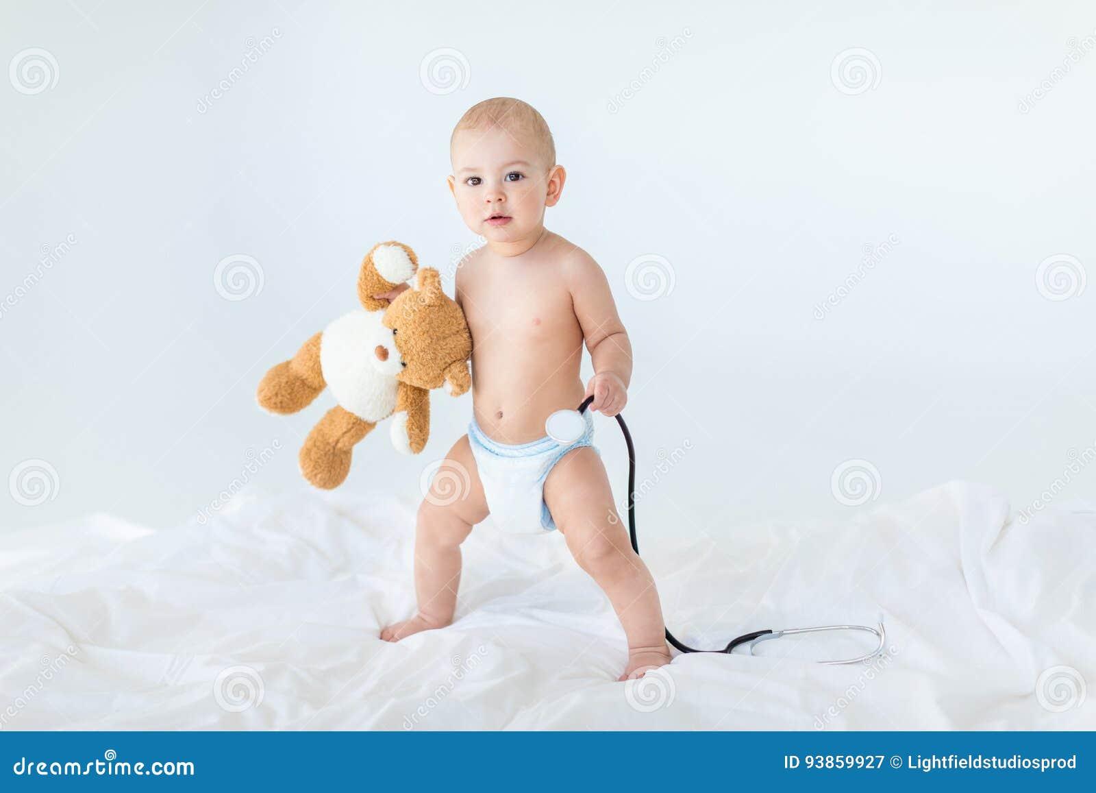 Förtjusande små behandla som ett barn pojkeanseende på säng- och innehavstetoskopet med nallebjörnen