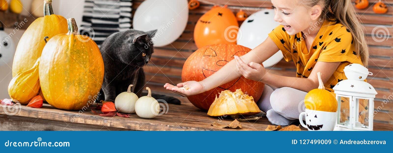 Förtjusande ung flickasammanträde på en tabell som spelar med halloween pumpa och hennes älsklings- katt Allhelgonaaftonlivsstilb