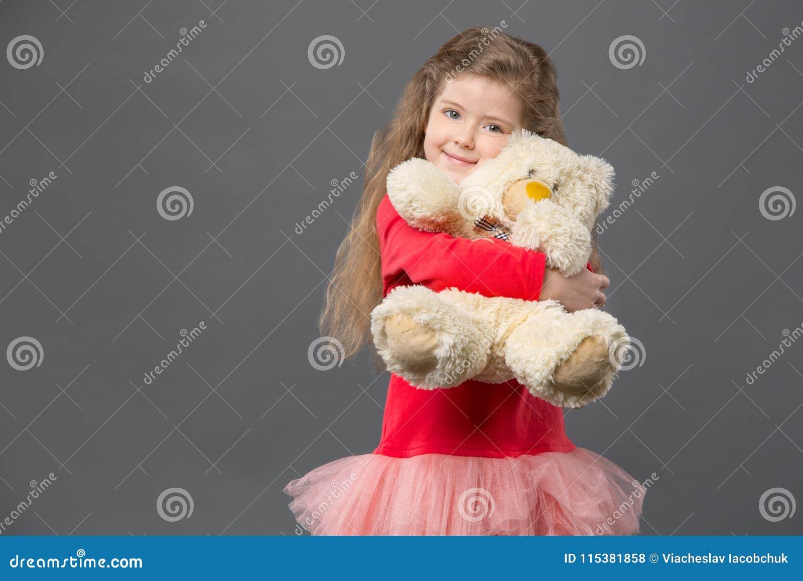 Förtjust gullig flicka som kramar hennes fluffiga björn