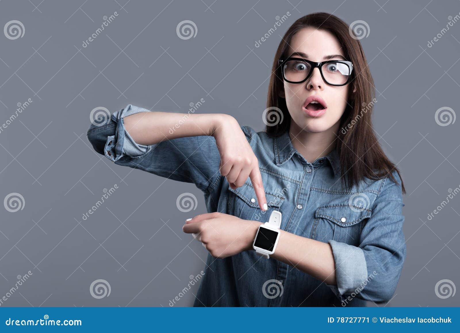 Förvånad bärande smartwatch för ung kvinna