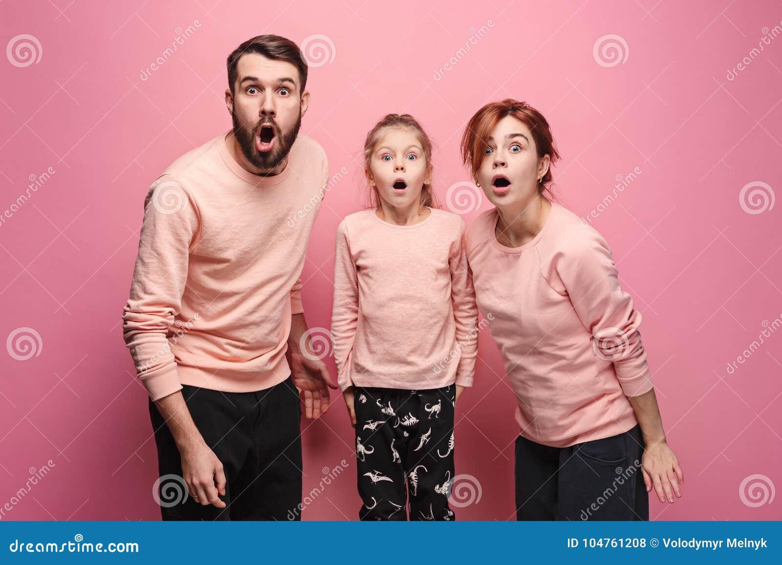 Förvånad ung familj som ser kameran på rosa färger